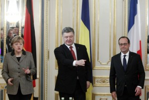 Ukraine's President Poroshenko gestures to German Chancellor Merkel and French President Hollande during their talks in Kiev